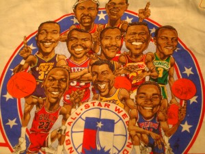 Official 1989 NBA All Star T-shirt featuring West Roster Magic Johnson, Karl Malone, Chris Mullin, Kareem Abdul-Jabbar, Hakeem Olajuwon, Clyde Drexler, John Stockton, James Worthy, Alex English, Dale Ellis, Mark Eaton, Tom Chambers & Kevin Duckworth and East Team with Michael Jordan, Moses Malone, Dominique Wilkins, Isiah Thomas, Charles Barkley, Terry Cummings, Kevin McHale, Larry Nance, Mark Jackson, Mark Price, Patrick Ewing, Brad Daugherty
