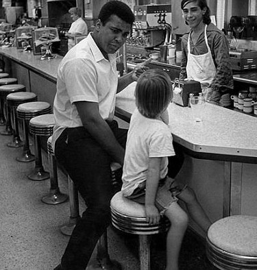 Photo of Muhammad Ali With Young Fan in a Diner, 1970