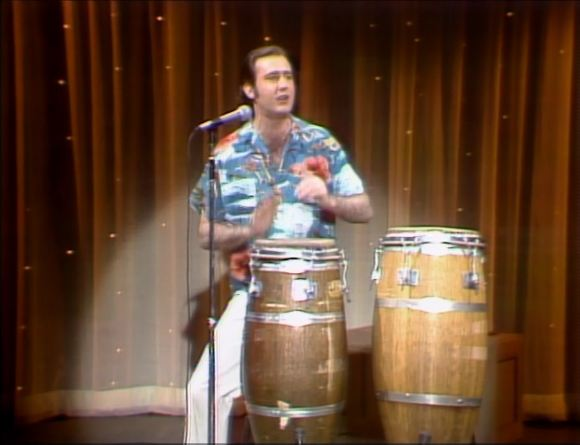 Photo of Comedy – 1979 – Special – Andy Kaufman – Playing Bongos + Speaking In Foreign Tongues